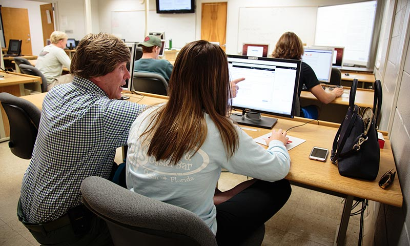 Instructor working with a student on a computer