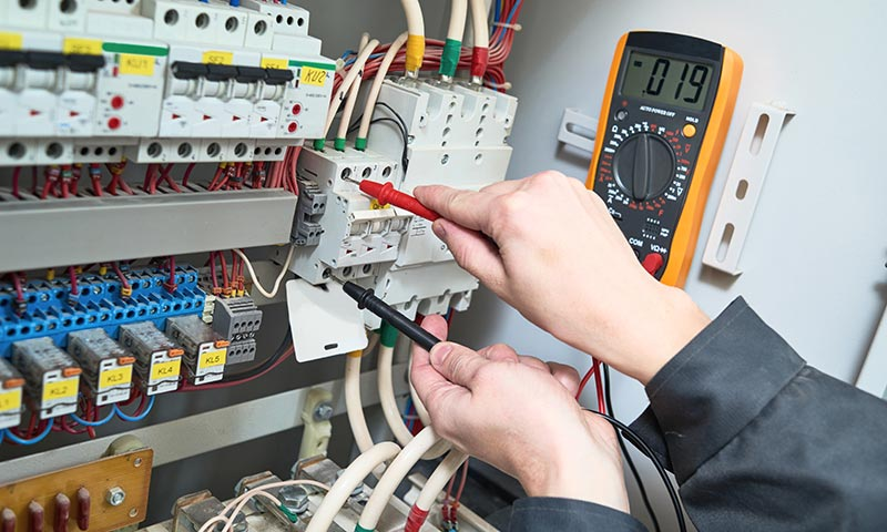 A technician checking an electrical circuit breaker